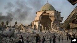 ជនស៊ីវិលអ៊ីរ៉ាក់ដែលរត់ភៀសខ្លួនដើរកាត់វិហារឥស្លាមអាល់ នូរី (al-Nuri) នៅពេលដែលកងកម្លាំងអ៊ីរ៉ាក់បន្តវាយប្រហារលើយុទ្ធជនរដ្ឋឥស្លាមនៅក្នុងក្រុង Mosul ប្រទេសអ៊ីរ៉ាក់ កាលពីថ្ងៃទី៤ ខែកក្កដា ឆ្នាំ២០១៧។
