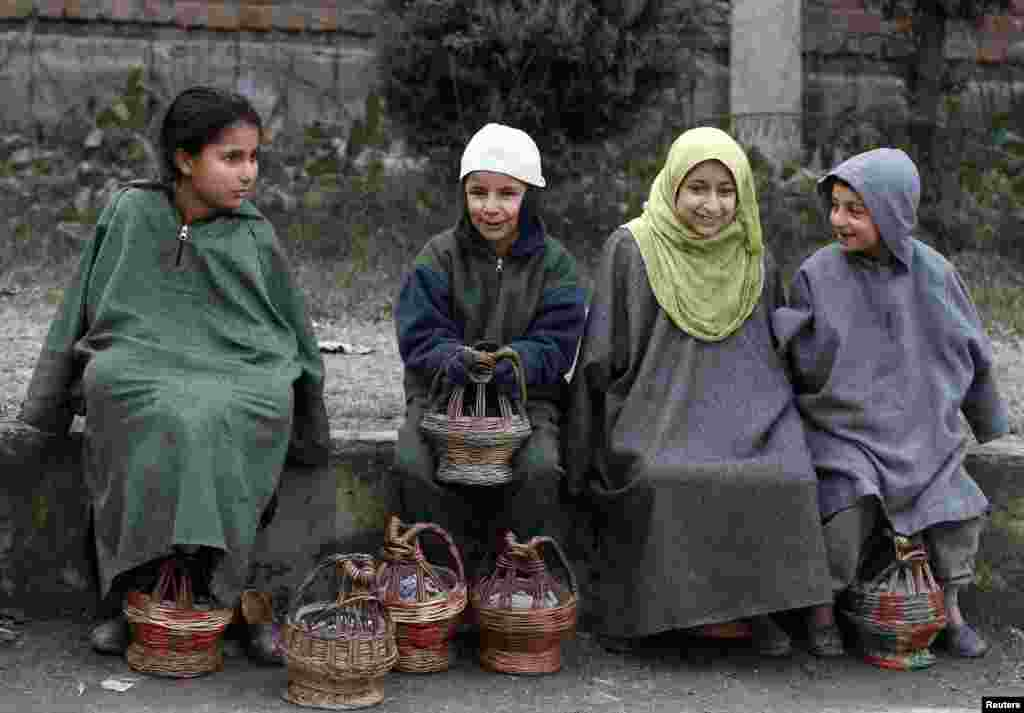 "Kashmiri children warm themselves using ""Kangris"", or traditional fire pots, as they sit outside a polling station on a cold winter morning during the fourth phase of the state assembly election in Srinagar, India."