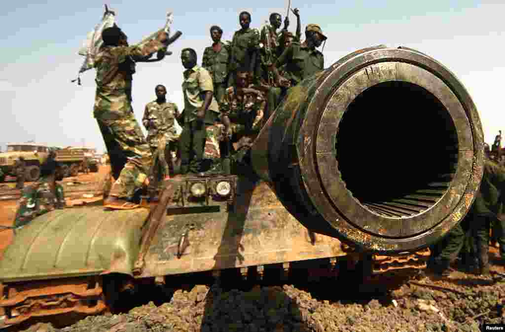 Sudanese military soldiers stand at a Sudan People's Liberation Army (SPLA) tank during the visit of Sudanese President Omar al-Bashir (not seen) in Heglig, April 23, 2012. (Reuters)