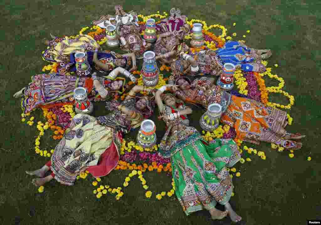 ស្ត្រីៗស្លៀកពាក់ក្នុងសម្លៀកបំពាក់ប្រពៃណីដេកនៅស្ងៀម បន្ទាប់ចូលរួមក្នុងការហាត់សមសម្រាប់របាំ Garba មុខពិធីបុណ្យ Navratri នៅក្នុងក្រុង Ahmedabad ប្រទេសឥណ្ឌា។ ពិធីបុណ្យ Navratri ដែលត្រូវបានប្រារព្ធឡើងដើម្បីឧទ្ទិសដល់ព្រះ Durga ត្រូវបានគេប្រារព្ធក្នុងរយៈពេល៩ថ្ងៃ នៅកន្លែងដែលយុវជនរាប់ពាន់នាក់រាំក្នុងពេលរាត្រីក្នុងសម្លៀកបំពាក់ប្រពៃណី។