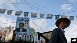A man walks on a street backdropped by a wall of campaign posters promoting presidential and mayoral candidates, in Patzun, Guatemala, Sept 4, 2015.