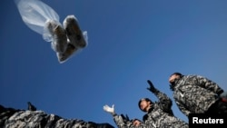 Former North Korean defectors who were soldiers when they lived in North Korea release a balloon containing $1 banknotes, radios, CD and leaflets denouncing the North Korean regime towards the north near the demilitarized zone, which separates the two Koreas, in Paju, north of Seoul, Jan. 15, 2014.