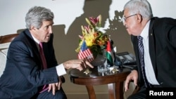 U.S. Secretary of State John Kerry (L) and Palestinian President Mahmoud Abbas talk at a meeting at the presidential compound in the West Bank city of Ramallah, Jan. 4, 2014.