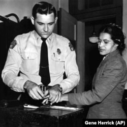 Rosa Parks is fingerprinted at a police station in Montgomery, Alabama, in 1955, after her arrest for refusing to give her bus seat to a white person