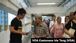 香港大學學生劉同學(左)自發在公共屋邨向街坊宣傳佔中全民投票