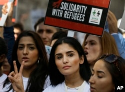 Demonstrators gesture and hold banners during a Solidarity with Refugees march from Marble Arch to Parliament in London, Sept. 12, 2015.
