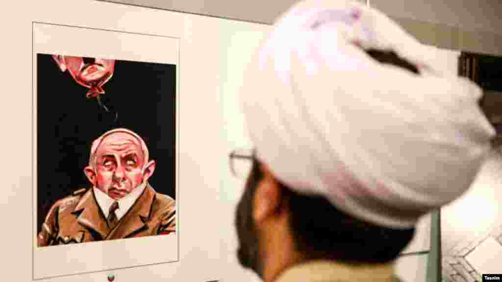 یک روحانی در دومین نمایشگاه بینالمللی کارتون و کاریکاتور هولوکاست که عملا به انعکاس آثاری در نفی و تمسخر هولوکاست می پردازد.