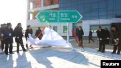 South and North Korean officials unveil the sign of Seoul to Pyeongyang during a groundbreaking ceremony for the reconnection of railways and roads at the Panmun Station in Kaesong, North Korea, December 26, 2018.