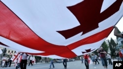 FILE - Georgians carry a giant national flag during a 2008 demonstration in Tbilisi, Georgia.