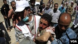 Paramedis membawa seorang korban pasca-bentrokan dengan polisis di Sana'a, Yaman (15/10).