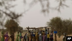 FILE - Women crowd a well in the village of Kiral, near Goudoude Diobe in the Matam region of northeastern Senegal.
