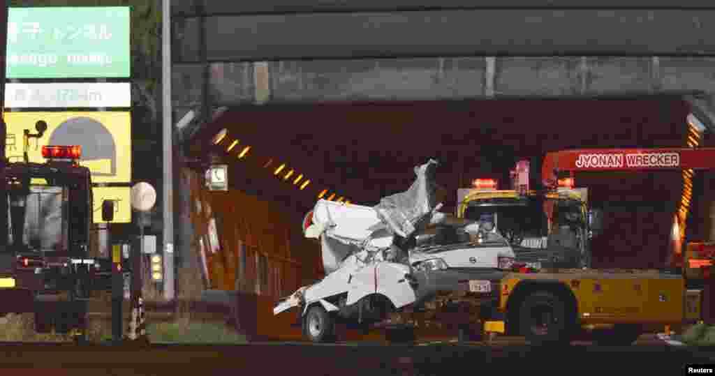 Chiếc xe bị hư hại được kéo đi khỏi đường hầm Sasago, quận Yamanashi, sau khi nằm kẹt trong hầm một ngày. (Kyodo)
