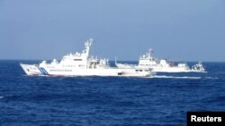 Chinese marine surveillance ship Haijian No. 51 (R) cruises next to a Japan Coast Guard patrol ship, Akaishi, in the East China Sea near the disputed isles known as Senkaku isles in Japan and Diaoyu islands in China, Feb. 4, 2013.