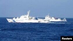 日本巡邏船(左)與中國海監船(右)在有爭議島嶼水域對峙並行。(路透社圖片 2013年2月由日本海岸警衛隊發表)