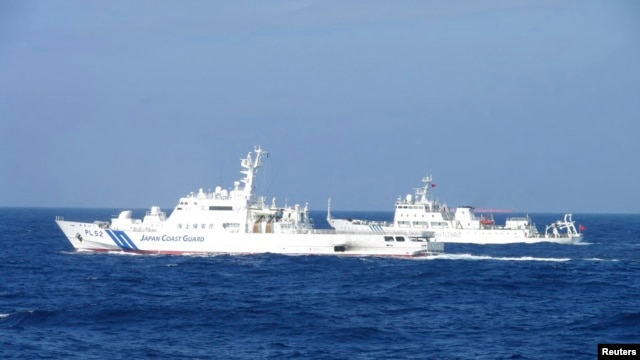 Chinese marine surveillance ship Haijian No. 51 (R) cruises next to a Japan Coast Guard patrol ship, Akaishi, in the East China Sea near the disputed isles known as Senkaku isles in Japan and Diaoyu islands in China, February 4, 2013.