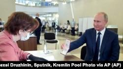 ប្រធានាធិបតីរុស្ស៊ីលោក Vladimir Putin បង្ហាញលិខិតឆ្លងដែនទៅកាន់មន្រ្តីគណៈកម្មការរៀបចំការបោះឆ្នោត នៅមណ្ឌលបោះឆ្នោតមួយ ក្នុងក្រុងមូស្គូ ប្រទេសរុស្ស៊ី កាលពីថ្ងៃទី០១ ខែកក្កដា ឆ្នាំ២០២០។