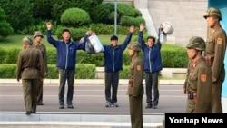 한국 동해상에서 구조된 북한 주민 3명이 5일 판문점을 통해 북으로 돌아간 뒤 만세삼창을 부르고 있다.