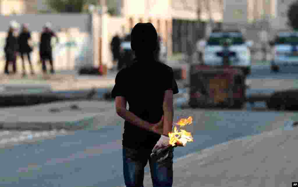 An anti-government protester prepares to throw a gasoline bomb at riot police during clashes in Malkiya village, Bahrain, January 7, 2013.