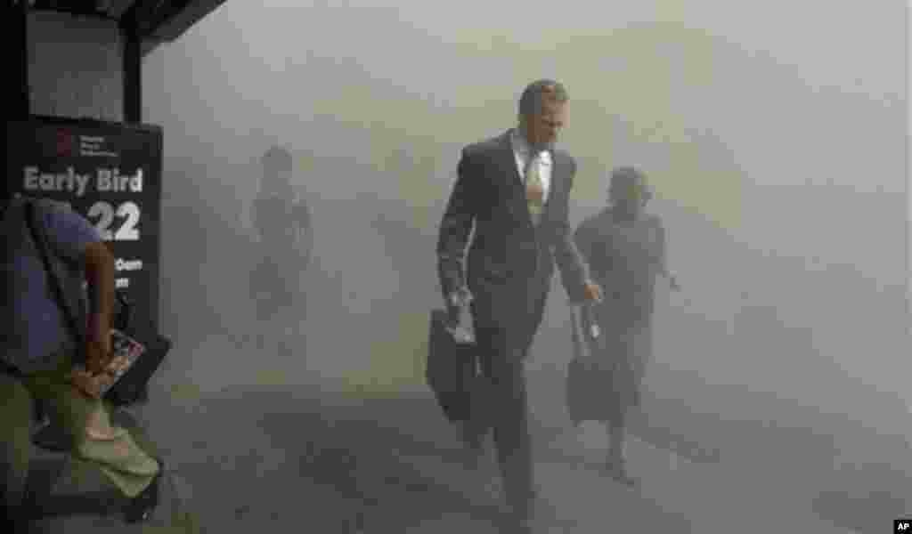 In this Tuesday, Sept. 11, 2001 file photo, pedestrians flee the dust-filled area surrounding the World Trade Center following a terrorist attack on the New York landmark. (AP Photo/Amy Sancetta)