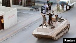 Pejuang Islam militan mengambil bagian dalam parade militer di sepanjang jalan-jalan di provinsi Raqqa utara 30 Juni 2014. (Foto: Reuters)