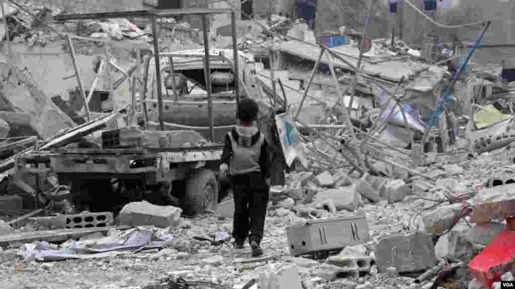 Yaro dan Syria yana tafiya a gefen burbushi da wata lalataciyyar mota a kauyen Hazzeh dake gabashin Ghouta a wajen garin Damascuss.