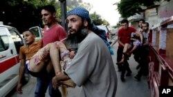 Warga Palestina menggendong seorang anak yang terluka dalam serangan Israel di Gaza, menuju ambulans hari Rabu (30/7).