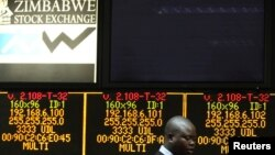 A Zimbabwe Stock Exchange official walks past an electronic display screen showing an 11-percent drop at the close of trading, Harare, Aug. 5, 2013.