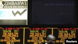 FILE: A Zimbabwe Stock Exchange official walks past an electronic display screen showing an 11-percent drop at the close of trading, in Harare, Zimbabwe, August 5, 2013.
