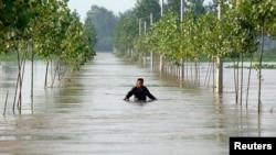 中國安徽王家壩地區的一名村民在被洪水淹沒的道路上行走。 (2020年7月10日)