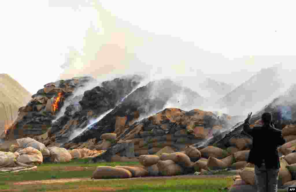 Sacks of wheat burn following air strikes by Syrian regime forces in the town of Ras al-Ain near the border with Turkey on November 16, 2012.