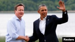 Britain's Prime Minister David Cameron (L) welcomes U.S. President Barack Obama on his arrival to the Lough Erne golf resort where the G8 summit is taking place in Enniskillen, Northern Ireland,l June 17, 2013.