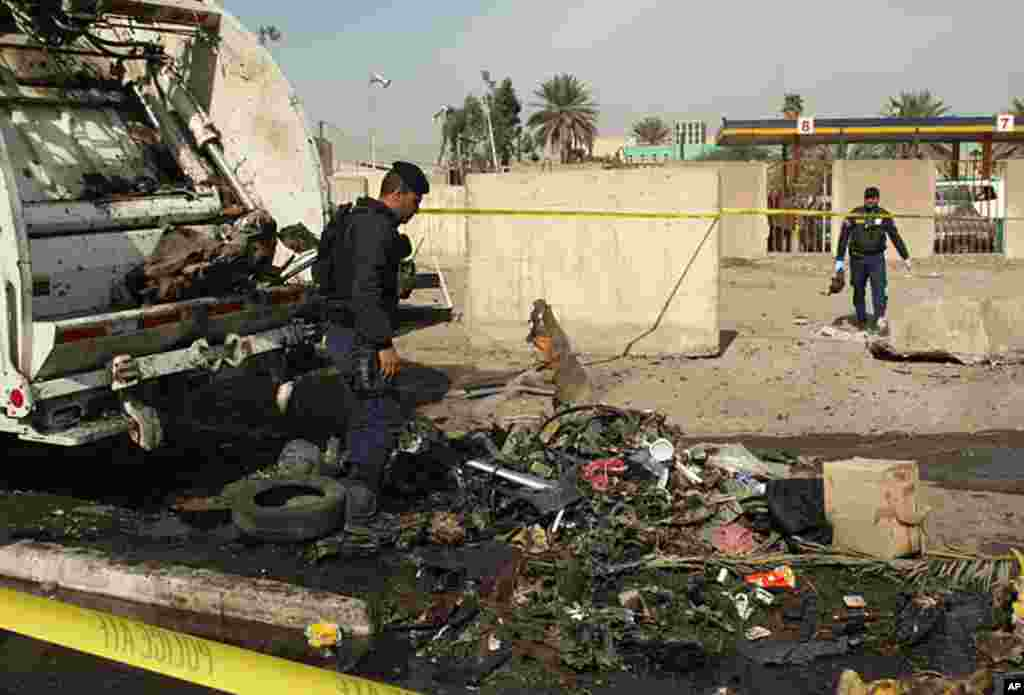 Iraqi security forces collect debris following a blast in Mansur in west Baghdad on February 23, 2012.(AFP)