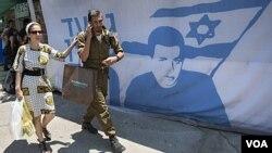 Warga Israel melewati tenda demonstran yang menyerukan pembebasan Gilad Schalit di Yerusalem (24/6).