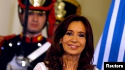 FILE - Argentina's President Cristina Fernandez de Kirchner smiles during a ceremony on her last day in office at the Casa Rosada Presidential Palace in Buenos Aires, Argentina.