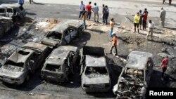 Warga berdiri di dekat lokasi ledakan bom di wilayah al-Shaab, Baghdad (27/10).