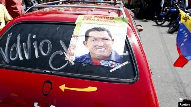 Pendukung Presiden Hugo Chavez di Caracas memasang foto Chavez di mobilnya dengan tulisan: 'Dia Telah Kembali', Senin (18/2).