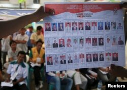 FILE - People watch as electoral officials show ballot papers during vote counting at a polling station in Jakarta April 9, 2014.