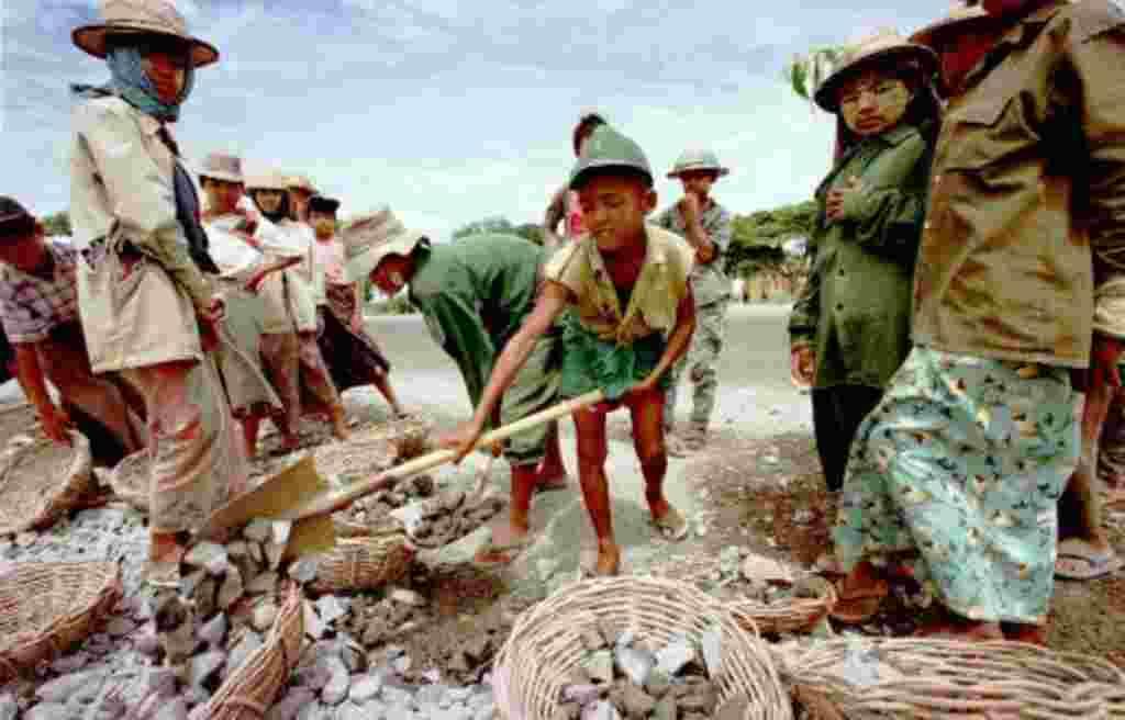 Un niño birmano traslada las rocas mientras trabajaba en una cuadrilla de construcción de la carretera en una autopista fuera de Rangún, Birmania. A los niños involucrados en el proyecto se les paga una tarifa diaria de 40 kyats ($30 centavos de dólar).
