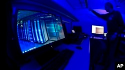 A member of the Cybercrime Center turns on the light in a lab during a media tour at the occasion of the official opening of the Cybercrime Center at Europol headquarters in The Hague, Netherlands, Friday Jan. 11, 2013.