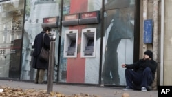 Một người vô gia cư ngồi trước cửa một ngân hàng ở Paris.