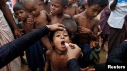 Seorang anak pengungsi Rohingya sedang menerima vaksinasi oral kolera yang dibagikan oleh Organisasi Kesehatan Dunia (WHO) dengan bantuan relawan dan LSM setempat, di Cox's Bazar, Bangladesh, 11 Oktober 2017. (Foto: Reuters)