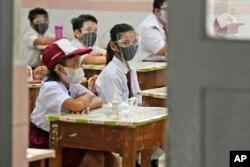 Siswa yang memakai masker saat mengikuti pelajaran hari pertama pembukaan kembali sekolah di sebuah sekolah dasar di Jakarta, Senin, 30 Agustus 2021. (Foto: AP)