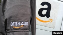 FILE - An Amazon.com Inc driver stands next to an Amazon delivery truck in Los Angeles, California, U.S.