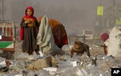 FILE - Afghan refugees girls collect recycle-able goods from a garbage to sell and earn living for their families in Peshawar, Pakistan, Feb. 5, 2016.