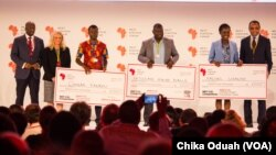 Dr. Conrad Tankou, Rachel Sibande and Dr. Abdoulaye Diallo stand on the stage at NEF holding the $25,000 checks that they won for their innovation prizes.