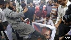 Người biểu tình đá vào tấm hình bị đốt của Tổng thống Syria Bashar Assad trong cuộc biểu tình trước trụ sở của Liên đoàn Ả Rập tại Cairo, Ai Cập