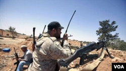 Pemberontak Libya melakukan komunikasi dengan 'walkie talkie' di salah satu posisi mereka di Misrata (9/6).