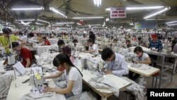 FILE - Laborers work at a garment factory in Bac Giang province, near Hanoi, Oct. 21, 2015. Vietnam's textiles and footwear would gain strongly from the Trans-Pacific Partnership, after exports of $31 billion last year for brands such as Nike, Adidas, H&M