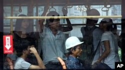 A commuter wears a construction helmet while sitting inside a crowded bus in Zhanjiang, China's Guangdong province, June 28, 2012.