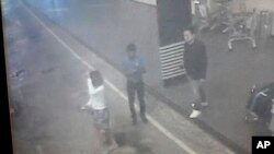 This image provided by Star TV, Feb. 15, 2017, of closed circuit television footage from Monday, Feb 13, 2017, shows a woman (left) at Kuala Lumpur International Airport in Sepang, Malaysia, who police say was arrested in connection with the death of Kim Jong Nam, the half brother of North Korean leader Kim Jong Un. (Star TV via AP)